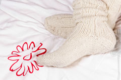 Legs in knitted warm socks Stock Photos