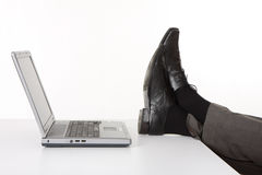 Legs with laptop on the desk Royalty Free Stock Photography