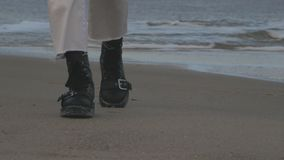 Legs in leather black shoes walk on the sand near the sea stock video
