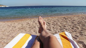 Legs lie on a sun lounger on the beach stock footage