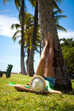 Legs like these need no explanation. Woman relaxing, lying on her back on the grass under palm tree in a park and holding up her beautifully toned legs. Travel royalty free stock photos