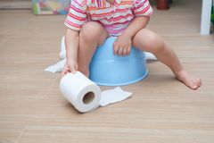 Legs of little Asian 2 years old toddler baby boy child sitting on blue potty holding, playing with toilet paper. Potty training stock photography