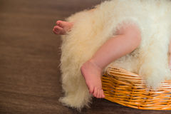 Legs a little baby in  basket Royalty Free Stock Photos