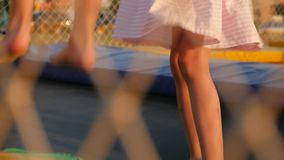Legs of little boy and girl running and jumping on the trampoline outdoors at evening stock video footage