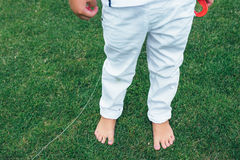 Legs of little boy in white jeans. Boy is standing on the grass. Child`s bare feet. Royalty Free Stock Photography