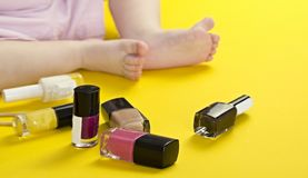 Legs of a little girl and cosmetics on a yellow background stock photos