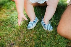 Legs of a little girl in striped shoes on the hands of the parent. royalty free stock images