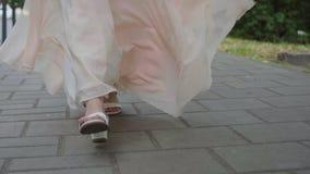 Legs in long dress walks around the city