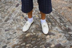 Legs of the lost man in white shoes and socks . Legs of the lost man in white shoes and socks on a stone pavement Stock Photography