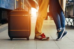 Legs Loving Couple happy hugging in the train station of a country after arrival in autumn with a warm sunlight. Legs Loving Couple happy hugging in the train Royalty Free Stock Photo