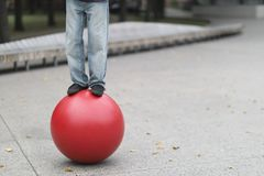 Legs of a man of a balancing actor. Standing on a big red ball stock photography