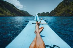 Legs of man on banca boat approaching tropical island. travel, relaxation and vacations concept.  royalty free stock photos