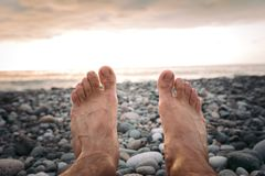 Legs of man on the beach at sunset. In sea stock photography
