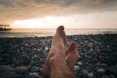 Legs of man on the beach at sunset. In sea royalty free stock photos