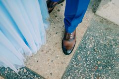 Legs of a man. In blue trousers and brown shoes royalty free stock photo