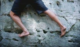 Legs of Man Climbing on the Sandstone Rock. Legs of Man Bouldering on the Sandstone Cliff royalty free stock image