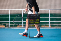 Legs of man in a closed tennis court with ball and racket Royalty Free Stock Photos