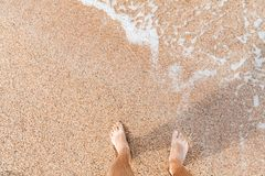Legs of a man on coastal sand. Barefoot legs of a man standing on coastal sand at sunny day, top view royalty free stock images