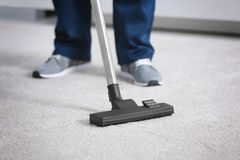 Legs of man hoovering carpet with cleaner Royalty Free Stock Photos