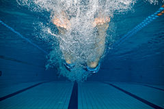 Legs of man jumping into pool. Young manjumping into pool. Concept of healthy lifestyle. Underwater photography Royalty Free Stock Photos