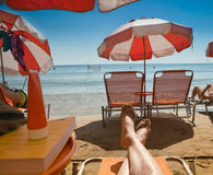 Legs of a man lying on a beach chair. In Agia Marina beach, Aegina Island, Greece stock photo
