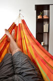 Legs of man lying down in bright hammock Royalty Free Stock Image