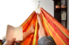 Legs of man lying down in bright hammock holding empty notice book in his hand Stock Image
