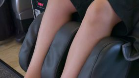 Legs of a man in a massage chair. Shin legs of a man are massaged in an electronic massage chair stock video