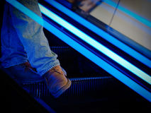 Legs of a man on moving stairs. Legs of a man who moves downward the moving stairs in a mall Stock Photo