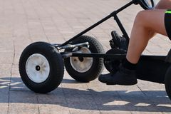 Legs of man riding on foot-operated four-wheeler. At sunny day Stock Images