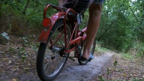 Legs of a Man in Rivets on a Bicycle Riding along a Path in the Forest. Slow Motion. In 96 fps. The camera is moving behind the bicycle. The pensioner is riding stock video