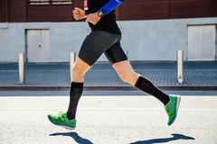 Legs man runner. Athlete in compression socks running marathon royalty free stock image