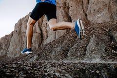 Legs man runner. Running on mountain stones trail royalty free stock image