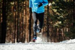 Legs man runner. Running winter trail snow flies spray royalty free stock photography