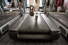 Legs of man running on treadmill in health club Stock Photography