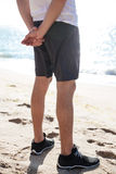 Legs of man in shorts and sneakers standing on beach Royalty Free Stock Photos