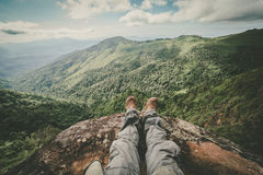 Legs of a man sitting on the edge of a cliff Royalty Free Stock Photo