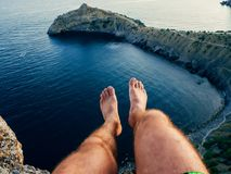 Legs of a man sitting on mountain above sea in tourist stock images
