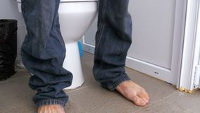 The Legs of a Man Sitting on the Toilet. A man in jeans and bare feet in a white toilet cubicle sits down on the toilet. Defecation process. Toilet in a public stock video footage