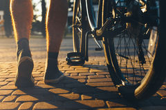 Legs of a man in sneakers and a city bicycle are moving about the cobbles against the background of bright sunlight during sunset. Royalty Free Stock Photo