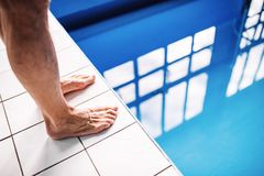 Legs of a man standing on the edge of the swimming pool. Unrecognizable man going to jump in the water Stock Photography