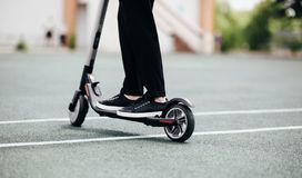 Legs of a man in stylish outfit stand on electric scooter on the street stock images