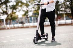 Legs of a man in stylish outfit stand on electric scooter on the street stock photography