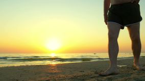 Legs of a man walking along a sea sandy beach in the background of a sunset. The legs of a Caucasian man. Slow motion.  stock footage