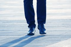 Legs of a man walking on a city street. The legs of a man walking on a city street royalty free stock images