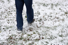 The legs of a man walking in the snow. stock photo