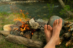 The legs of a man warming themselves by the campfire outdoors Stock Images