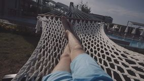 The guy lies in a hammock. Legs of a man who lies in a hammock close-up stock video footage