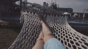 The guy lies in a hammock. Legs of a man who lies in a hammock close-up stock footage
