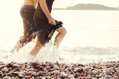Legs of a man and a woman in a black dress running across the sea. Splashing water against the setting sun stock image